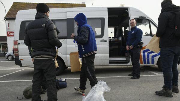 Migrants, who were arrested earlier in Belgium, are released by Belgian police officers near the Belgian-French border on February 26, 2016 in Adinkerke. - Sputnik International