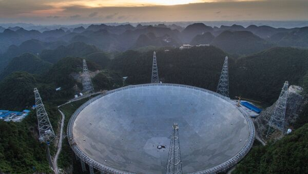 In this photo released by China's Xinhua News Agency, the sun sets above the Five-hundred-meter Aperture Spherical Telescope (FAST) in Pingtang County in southwestern China's Guizhou Province Monday, June 27, 2016 - Sputnik International