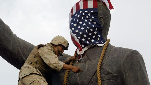 A US Marine covers the head of a statue of Iraqi President Saddam Hussein with the US flag before pulling it down in Baghdad's al-Fardous (paradise) square 09 April 2003 as the marines swept into the Iraqi capital and the Iraqi leader's regime collapsed. - Sputnik International