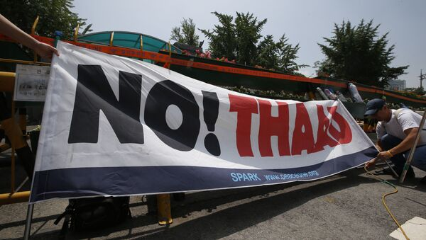 A South Korean protester ties a banner before a rally to denounce deploying the Terminal High-Altitude Area Defense, or THAAD, in front of the Defense Ministry in Seoul, South Korea, Friday, July 8, 2016. - Sputnik International