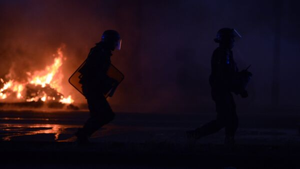 French riot police walk near a fire during the Euro 2016 final football match between Portugal and France at the Champ-de-Mars fan zone in Paris on July 10, 2016. Ronaldo's Portugal beat France 1-0 in Euro 2016 final. - Sputnik International