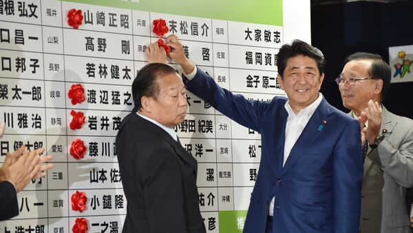 Japanese Prime Minister and ruling Liberal Democratic Party (LDP) president Shinzo Abe (C) places a red paper rosette on an LDP candidate's name to indicate an election victory at the party's headquarters in Tokyo on July 10, 2016 - Sputnik International