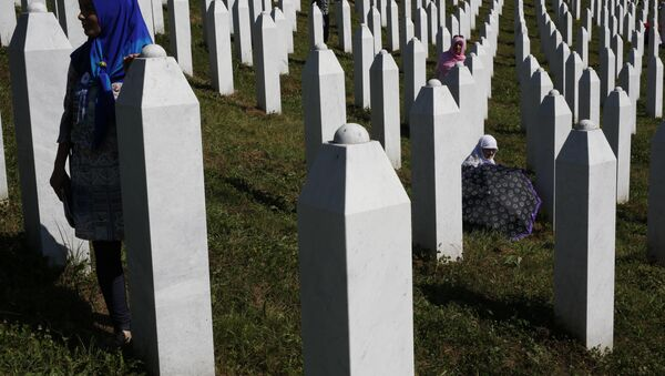 A Bosnian woman prays next to a coffin containing the remains of her relative perished in the Srebrenica massacre, during a funeral ceremony for the 127 victims at the Potocari memorial complex near Srebrenica, 150 kilometers (94 miles) northeast of Sarajevo, Bosnia and Herzegovina, Monday, July 11, 2016 - Sputnik International