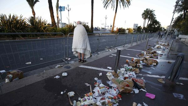 A man walks through debris scatterd on the street the day after a truck ran into a crowd at high speed killing scores celebrating the Bastille Day July 14 national holiday on the Promenade des Anglais in Nice, France, July 15, 2016. - Sputnik International