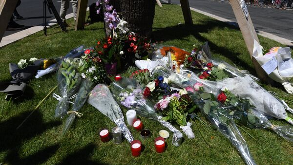 A photo taken on July 15, 2016 shows flowers and candles placed near the site in Nice where a gunman smashed a truck into a crowd of revellers celebrating Bastille Day, killing at least 84 people. - Sputnik International