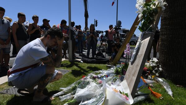 A man kneels and holds his head on July 15, 2016 in front of flowers placed near the site in Nice where a gunman smashed a truck into a crowd of revellers celebrating Bastille Day, killing at least 84 people. - Sputnik International