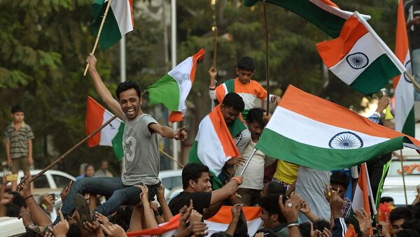 Indian fans wave national flags as they celebrate after India won the 2015 Cricket World Cup's cricket match against Pakistan, on the streets of Mumbai - Sputnik International
