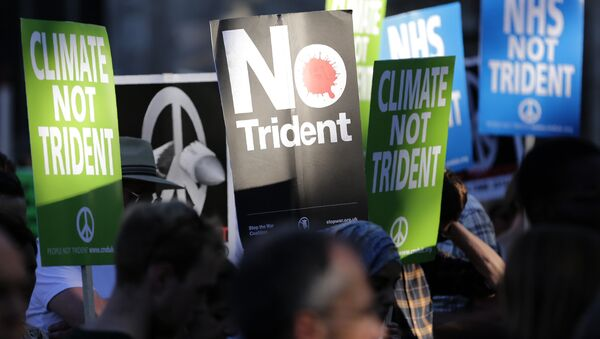 Demonstrators hold placards calling for government funds to be spent on the NHS and climate change, as they attend an anti-war and anti-trident demonstration near the Houses of Parliament in central London on July 18, 2016 - Sputnik International