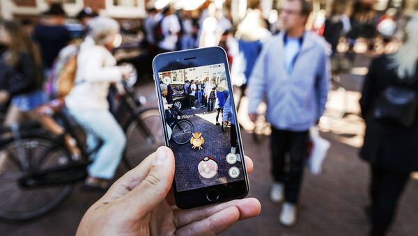 Gamers play with the Pokemon Go application on their mobile phone, at the Grote Markt in Haarlem, on July 13, 2016 - Sputnik International