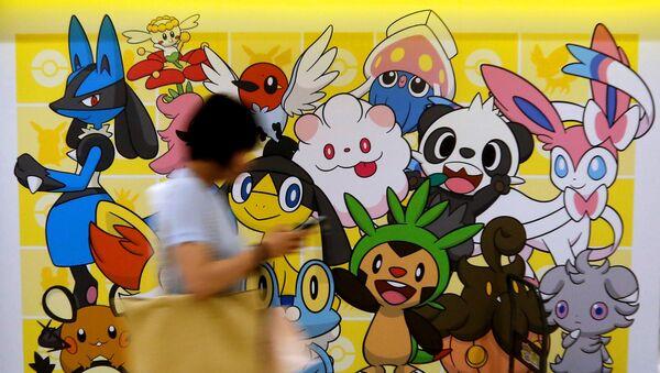 A woman using a mobile phone walks past a shop selling Pokemon goods in Tokyo, Japan July 20, 2016. - Sputnik International