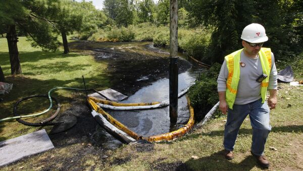 In this July 29, 2010 file photo, a worker monitors the water in Talmadge Creek in Marshall Township, Mich., near the Kalamazoo River as oil from a ruptured pipeline, owned by Enbridge Inc, is vacuumed out the water - Sputnik International