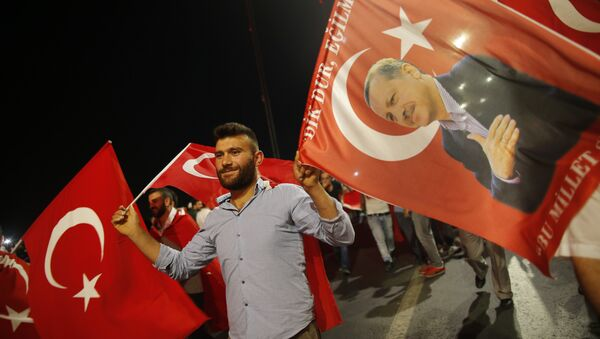 A pro-government supporter waves a Turkish flag and one with the picture of Turkey's President Recep Tayyip Erdogan, right, during a rally on the road leading to Istanbul's iconic Bosporus Bridge, Thursday, July 21, 2016 - Sputnik International