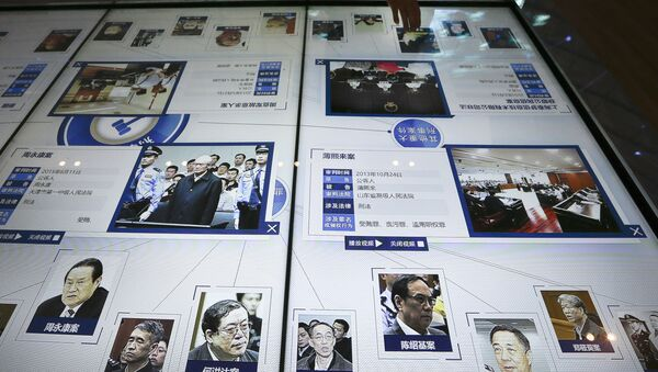 A visitor, top, looks at an electronic screen displaying images and convicted corruption charges of China's fallen politicians, Bo Xilai, bottom second right, Zhou Yongkang, bottom left, and other senior officials, at the China Court Museum in Beijing, Tuesday, Jan. 12, 2016 - Sputnik International