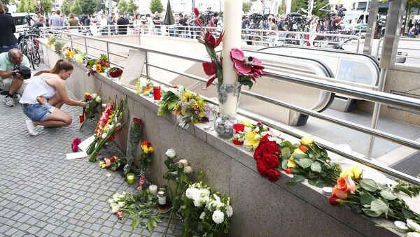 A women places flowers near the Olympia shopping mall, where yesterday's shooting rampage started, in Munich, Germany July 23, 2016. - Sputnik International
