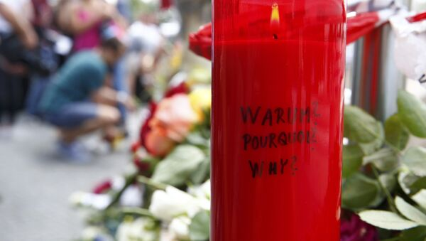 A candle with the words 'Why?' written upon it is placed next to flowers near the Olympia shopping mall, where yesterday's shooting rampage started, in Munich, Germany July 23, 2016. - Sputnik International