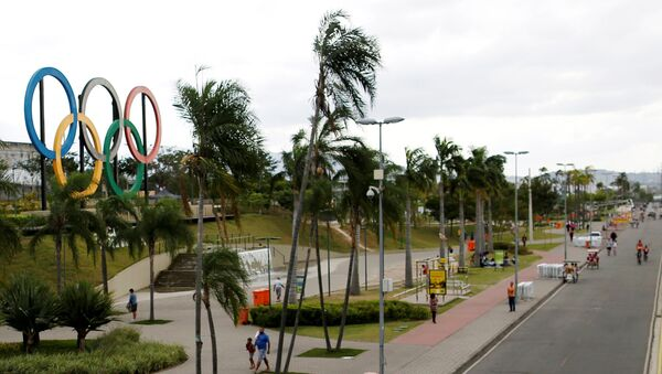 People walk near Olympic rings placed at Madureira Park ahead of the Rio 2016 Olympic Games in Rio de Janeiro, Brazil, July 17, 2016. - Sputnik International