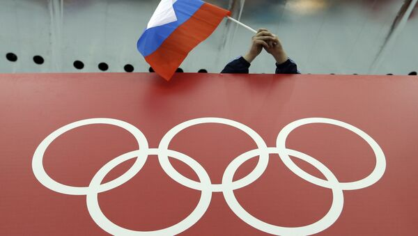Russian skating fan holds the country's national flag over the Olympic rings before the start of the men's 10,000-meter speedskating race at Adler Arena Skating Center during the 2014 Winter Olympics in Sochi, Russia. (File) - Sputnik International