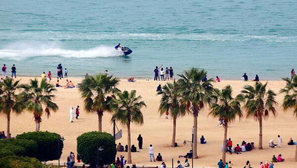 A jet-skier drives past people on a beach in the Salmiya district of Kuwait City - Sputnik International