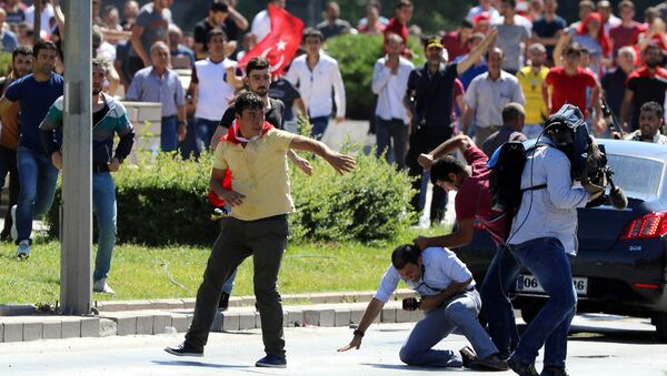 Supporters of Turkey's President Recep Tayyip Erdogan, who were staging a protest against a coup, clash with Turkish journalists near the Turkish military headquarters, in Ankara, Turkey, Saturday, July 16, 2016 - Sputnik International