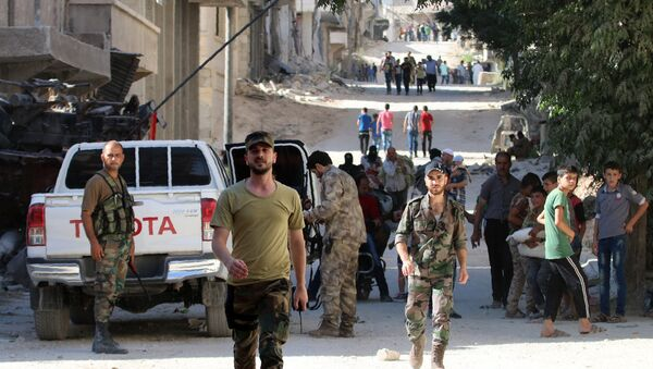 Syrian government forces secure a street as civilians walk on a street in the neighbourhood of Bani Zeid, on Aleppo's northern outskirts on July 29, 2016 - Sputnik International
