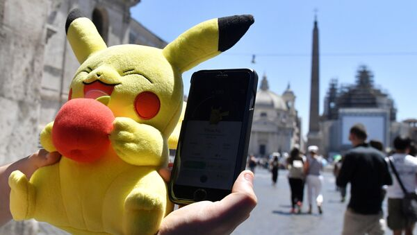 A gamer holds a Pokemon mascot and his mobile phone as he plays with the Pokemon Go application in central Rome on July 19, 2016 - Sputnik International