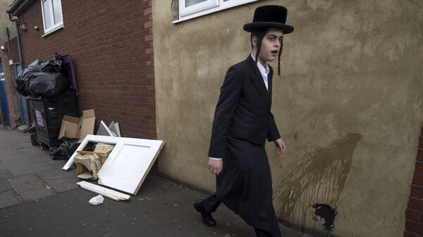 An Orthodox jew walks past a damaged door belonging to the Ahavas Torah synagogue in the Stamford Hill area of north London on March 22, 2015 - Sputnik International