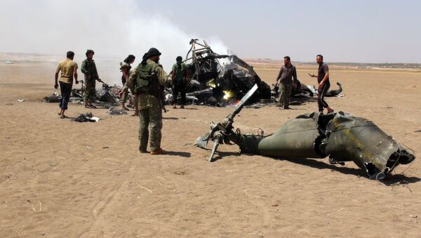A picture taken on August 1, 2016 shows Syrian rebels gathering around the wreckage of a Russian Mi-8 military transport helicopter after it was shot down along the administrative border between Idlib province, northwestern Syria and neighbouring Aleppo - Sputnik International