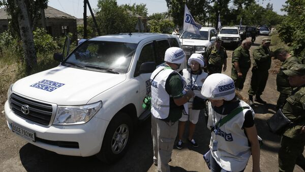 Members of the Organization for Security and Co-operation in Europe (OSCE) stand in the village of Shyrokyne, Donetsk region on July 4, 2015 - Sputnik International