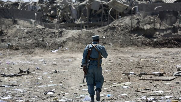 FILE - In this Monday, Aug. 1, 2016 file photo, an Afghan Security policeman inspects the site of a suicide truck bombing, in Kabul, Afghanistan. - Sputnik International