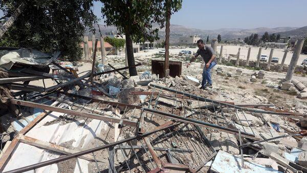 A Palestinian man walks amidst debris after Israeli authorities demolished a building in the village of Sebastia, near Nablus, in the Israeli-occupied West Bank on August 9, 2016 - Sputnik International