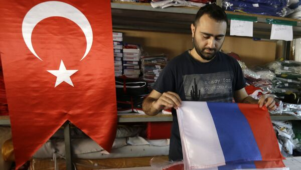 An employee of a flag-making factory folds a Russian flag as a Turkish flag adorns the display at left, in Istanbul, Tuesday, Aug. 9, 2016 - Sputnik International
