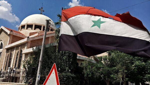 A state flag of the Syrian Arab Republic by an Orthodox church in an old Christian block of Aleppo, Syria - Sputnik International