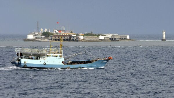 Chinese fishing vessel sails by Fiery Cross Reef, background, also known as Yongshu Reef, of the Spratly Islands in South China Sea. File photo. - Sputnik International
