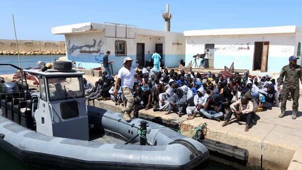 Illegal migrants sit on the dock at the Tripoli port after 117 migrants of African origins, including six pregnant women, were rescued by two coast guard boats off the coast of Libya on June 7, 2016 - Sputnik International