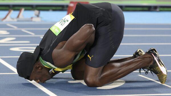 2016 Rio Olympics - Athletics - Final - Men's 4 x 100m Relay Final - Olympic Stadium - Rio de Janeiro, Brazil - 19/08/2016. Usain Bolt (JAM) of Jamaica kisses the track after his team won the gold - Sputnik International
