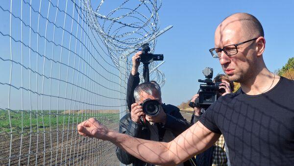Ukrainain Prime Minister Arseniy Yatsenyuk (R) touches a piece of gate as he visits a newly constructed section of the Ukrainian-Russian border, near the Goptivka border crossing, north of Kharkiv, eastern Ukraine, on October 15, 2014 - Sputnik International