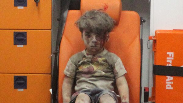 Five-year-old Omran Daqneesh, with bloodied face, sits inside an ambulance after he was rescued following an airstrike in the rebel-held al-Qaterji neighbourhood of Aleppo, Syria August 17, 2016. - Sputnik International