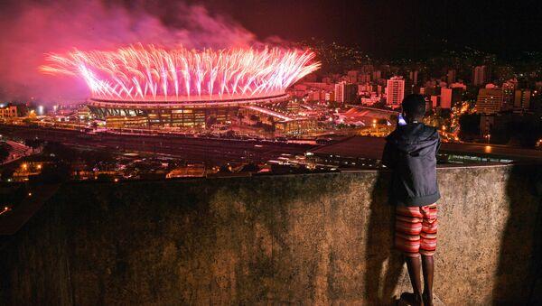 A boy from Mangueira favela watch fireworks over Maracana Stadium during the 2016 Olympics closing ceremony in Rio de Janeiro on August 21, 2016 - Sputnik International