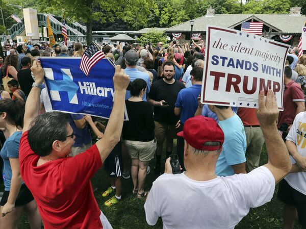A supporter of Democratic presidential candidate Hillary Clinton and a Republican presidential candidate Donald Trump supporter hold signs as they attend a Memorial Day parade Monday, May 30, 2016, in Chappaqua, N.Y. Clinton and her husband former President Bill Clinton, along with New York Gov. Andrew Cuomo, walked in the parade - Sputnik International