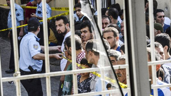 People stand near the explosion scene behind police cordon following a late night attack on a wedding party that left at least 30 dead in Gaziantep in southeastern Turkey near the Syrian border on August 21, 2016 - Sputnik International
