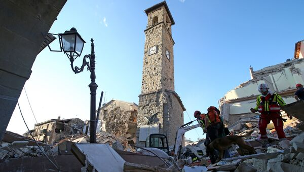 Rescuers walk past the bell tower with the clock showing the time of the earthquake in Amatrice, central Italy, August 24, 2016 - Sputnik International