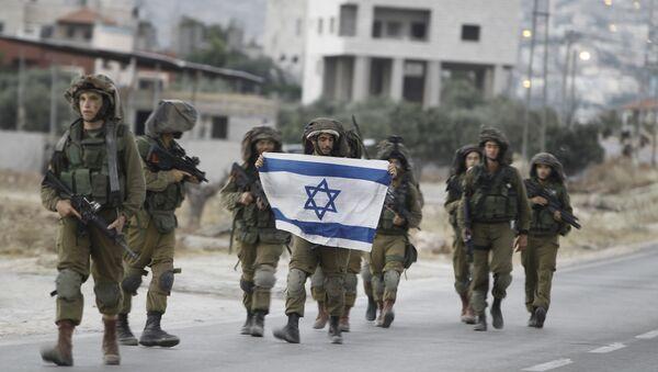 Israeli soldiers holding their national flag patrol a street in the West Bank village of Beit Furik, southeast of Nablus, early on June 20, 2014. - Sputnik International