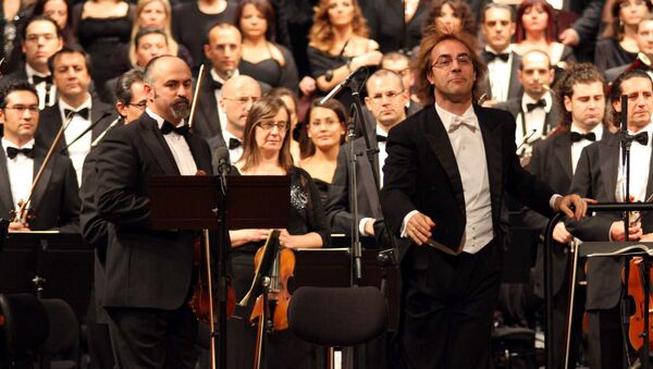 A view of the Bari province symphonic orchestra directed by Fabio Mastrangelo, at right in foreground, during a concert to mark the reopening of the Petruzzelli theatre, in Bari southern Italy. (File) - Sputnik International