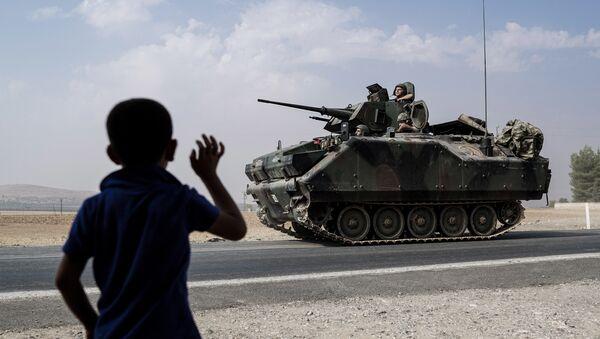 A child waves toward Turkish troops heading to the Syrian border, in Karkamis, Turkey, Friday, Aug. 26, 2016 - Sputnik International