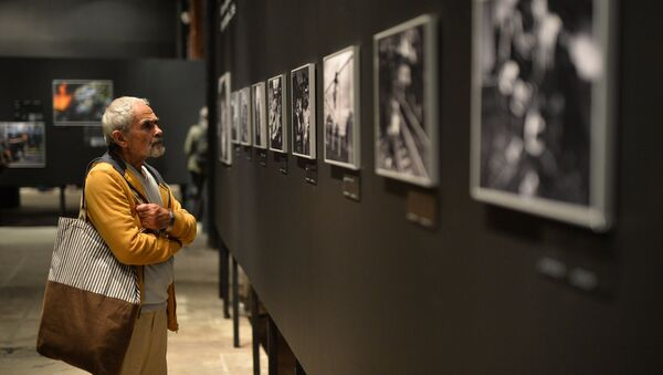 A visitor at the opening of a photo exhibition of the prizewinners in the Andrei Stenin International Press Photo Contest in Moscow. File photo - Sputnik International