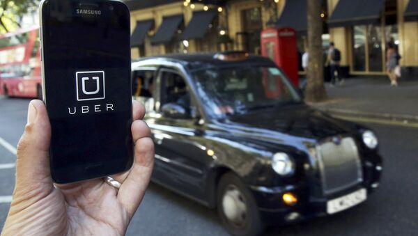 A photo illustration shows the Uber app logo displayed on a mobile telephone, as it is held up for a posed photograph in central London, Britain August 17, 2016. - Sputnik International