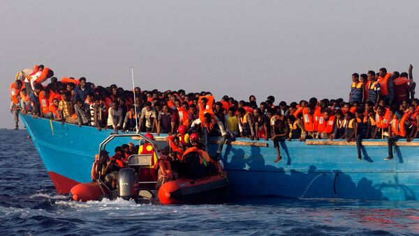 A rescue boat of the Spanish NGO Proactiva approaches an overcrowded wooden vessel with migrants from Eritrea, off the Libyan coast in Mediterranean Sea August 29, 2016 - Sputnik International