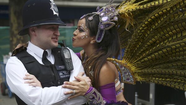 A performer dances with police during the Notting Hill Carnival in London, Britain August 29, 2016. - Sputnik International