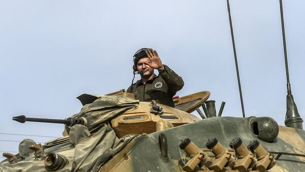 This picture taken around 5 kilometres west from the Turkish Syrian border city of Karkamis in the southern region of Gaziantep, on August 25, 2016 shows a soldier gesturing as Turkish Army tanks drive to the Syrian Turkish border town of Jarabulus - Sputnik International
