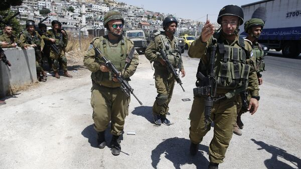 Israeli soldiers are seen at the site of a stabbing attack by a Palestinian man next to the entrance of the al-Arub refugee camp near the city of Hebron in the Israeli-occupied West Bank on July 18, 2016 - Sputnik International